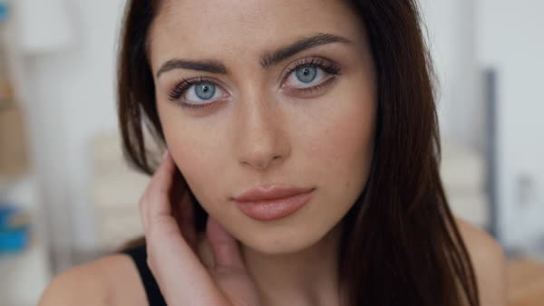 Portrait of a young woman with blue eyes touching her beautiful dark hair, close-up Royalty-free stock video