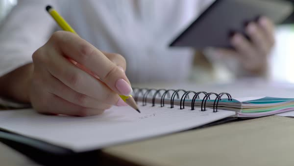 Close-up of female hand holding a pencil and writing some research notes in the appointment book Royalty-free stock video