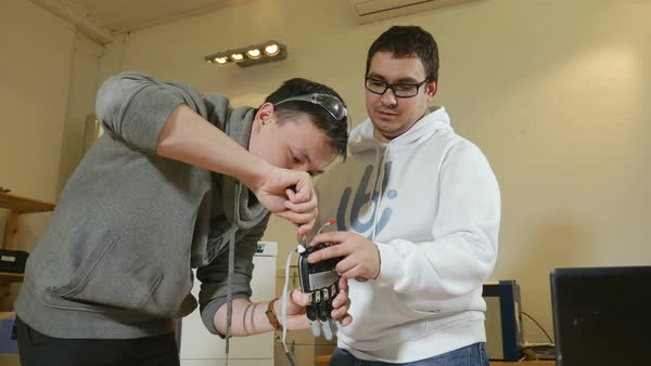 Two young engineers creating innovative cybernetic bionic arm. Hi-tech innovative technology. Royalty-free stock video