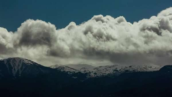 Timelapse shot of clouds flying over the snowy mountains eventually getting darker as mountain climate changes and storm approaches Royalty-free stock video