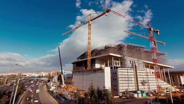 A wide view timelapse shot of a construction site with cranes working against the sky background Royalty-free stock video