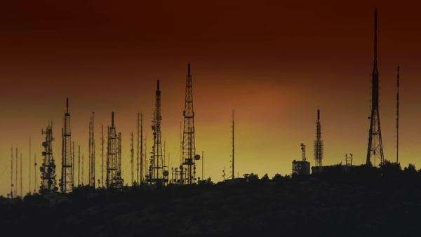 Telephoto shot of cell towers on top of a mountain at sunrise with gradient hues of red and yellow morning sky as background. Royalty-free stock video