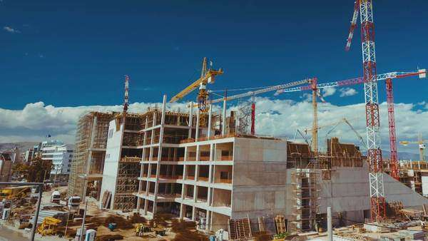 Big construction site with cranes panorama, post dolly timelapse. A close-up timelapse shot of a construction site. Machinery workers and cranes, against the sky background. Royalty-free stock video