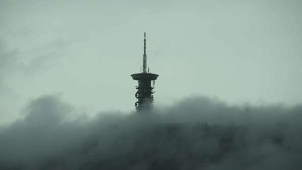 Communication, cellular, and broadcast towers site on top of a mountain, obscured by clouds fog and mist. Royalty-free stock video