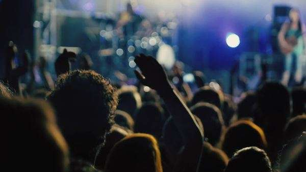 Conformed super slow motion clip at a night rock concert showing people having fun lifting hands up in the air and applauding the musicians. Royalty-free stock video
