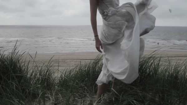 Medium wide shot of a young woman standing on a beach in the Netherlands Royalty-free stock video