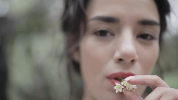 Close-up shot of a woman putting a white flower in her mouth Royalty-free stock video
