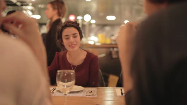 Medium shot of a woman sitting in a bar with other people Royalty-free stock video