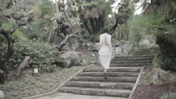 Wide shot of a woman walking up on stairs in a garden Royalty-free stock video