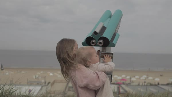 Hand-held shot of a girl holding a toddler up to an outdoor telescope Royalty-free stock video