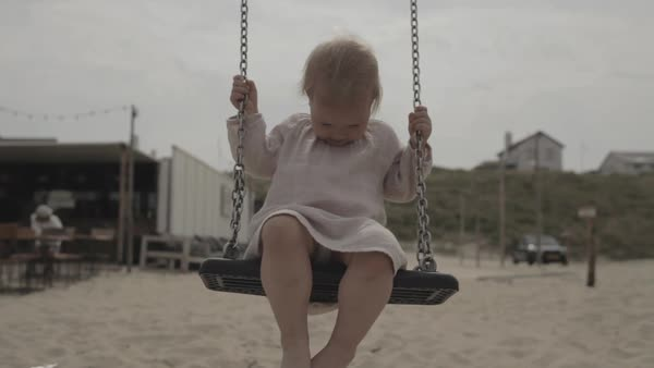 Hand-held shot of a toddler sitting on a swing Royalty-free stock video