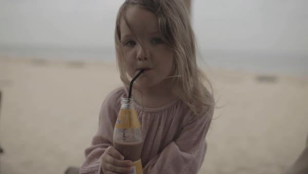 Hand-held shot of a girl drinking chocolate millk with a straw Royalty-free stock video