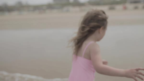 Hand-held shot of a girl standing on a beach then running away Royalty-free stock video