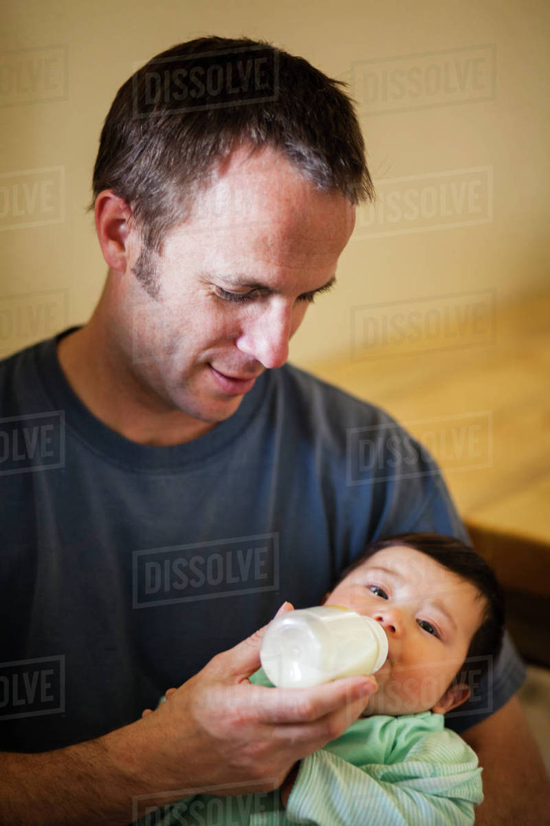 A man feeds a 4 month old Japanese American baby girl from a bottle of  breast milk  stock photo