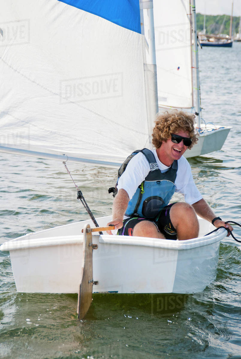 A man laughing sitting in small sailboat during a summer sailing camp stock  photo