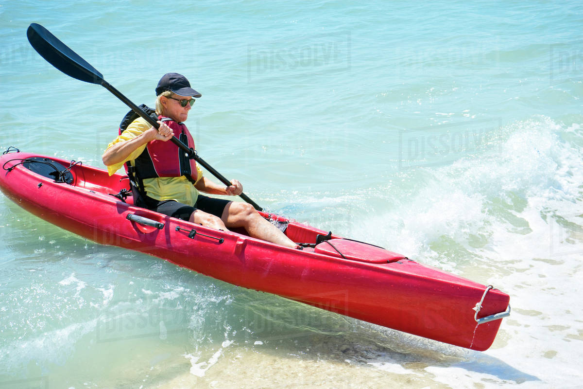 woman paddling a kayak in a wave stock photo dissolve
