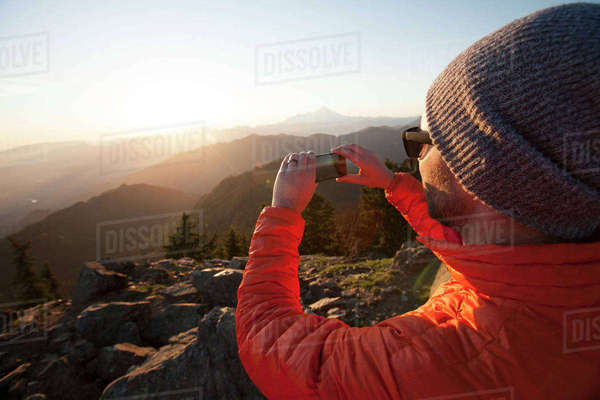 A hiker uses his smartphone to take a a picture of the view from the summit of Sauk Mountain. Royalty-free stock photo