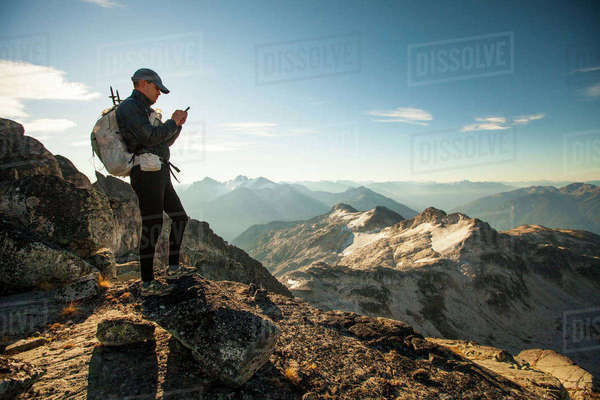 An ultralight backpacker sends a safety message from his smartphone while hiking high in the mountains near Whistler, BC, Canada. Royalty-free stock photo