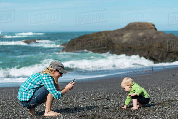 Mother taking smartphone photo of her young daughter playing on the beach.   California Coast Royalty-free stock photo