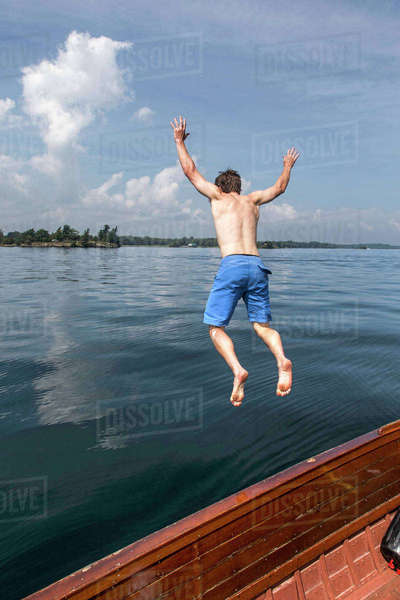 Man Jumping From An Antique Wooden Boat In The Saint Lawrence River Royalty-free stock photo