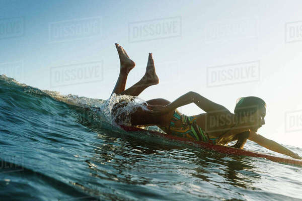 A Surfer Girl In A Bikini Paddles In A Wave Royalty-free stock photo