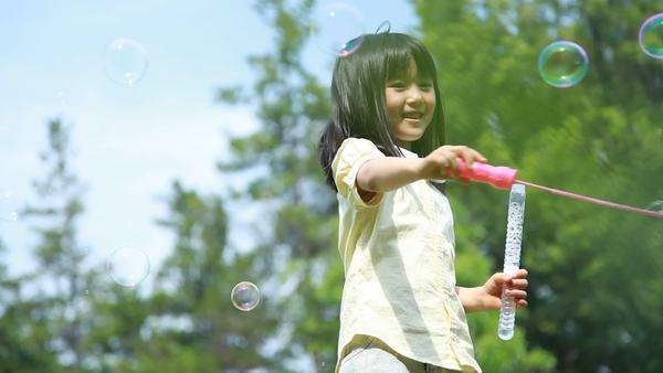 Japanese young girl playing with soap bubbles in a park, Tokyo, Japan Royalty-free stock video