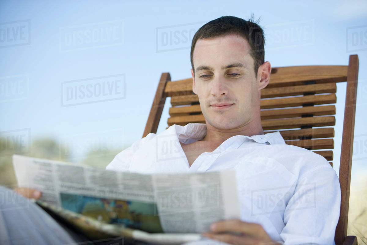 young man reading newspaper in deckchair - stock photo - dissolve