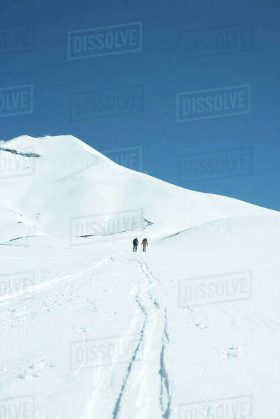 Skiers heading toward mountain, rear view Royalty-free stock photo