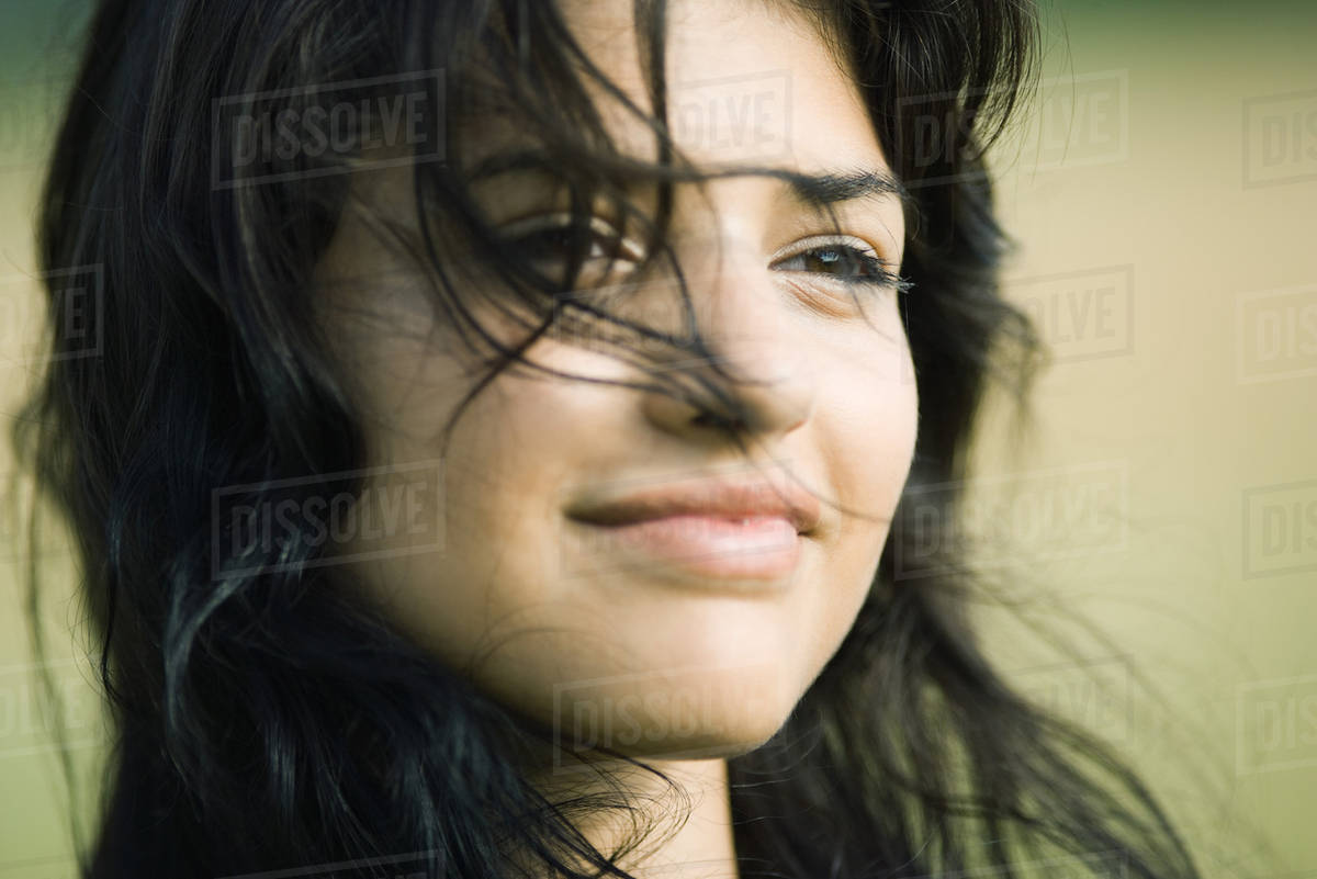 Young woman with hair blowing across her face, smiling, portrait Royalty-free stock photo