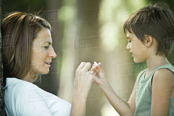 Mother and son sitting outdoors, playing together Royalty-free stock photo