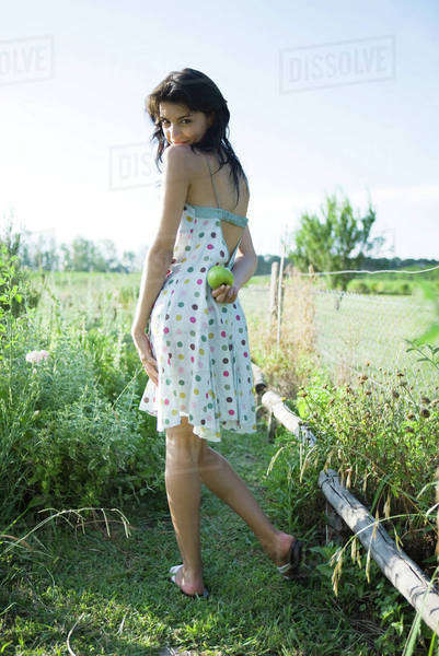 Young woman standing in garden, holding apple behind back, looking over shoulder at camera Royalty-free stock photo