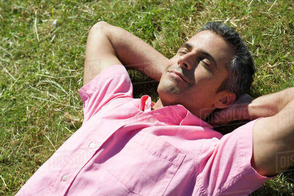 Man lying on grass with hands behind head and eyes closed Royalty-free stock photo