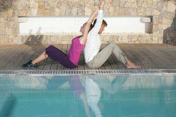 Young couple sitting back to back at poolside stretching Royalty-free stock photo