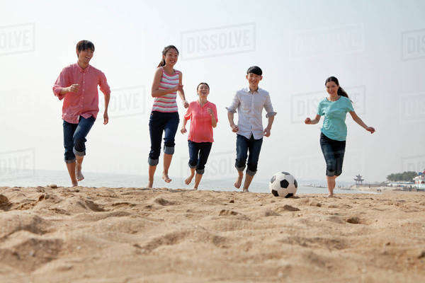 Young Friends Playing Soccer on the Beach Royalty-free stock photo