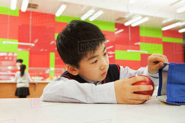 School boy checking lunch bag in school cafeteria Royalty-free stock photo