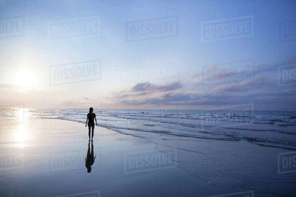 Woman walking on beach at sunrise Royalty-free stock photo