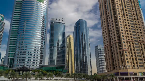 Timelapse view on skyscrapers at waterfront. Residential buildings in Jumeirah Lake Towers reflected in water in Dubai, UAE. View with blue cloudy sky from embankment Royalty-free stock video