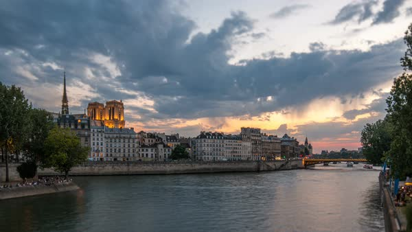 People and boats day to night transition timelapse with Notre Dame de Paris, Le Pont D'Arcole bridge after sunset, Paris, France, Europe. Colorful sky at summer day with reflection on river Seine. Tilt-shift lens Royalty-free stock video
