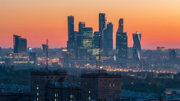View from top of cityscape night to day transition timelapse, residential buildings, park areas, group of Moscow City skyscrapers in distance, horizon, morning mist before sunrise, Moscow, Russia. Aerial view from rooftop on Leninskiy avenue Royalty-free stock video