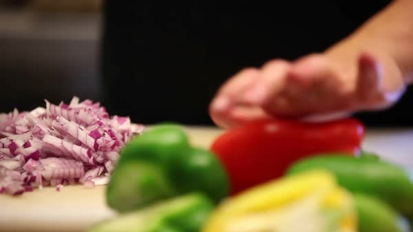 Person cutting slicing big green pepper. Person slicing yellow pepper. Woman cutting peppers and veggies. Series of takes Royalty-free stock video
