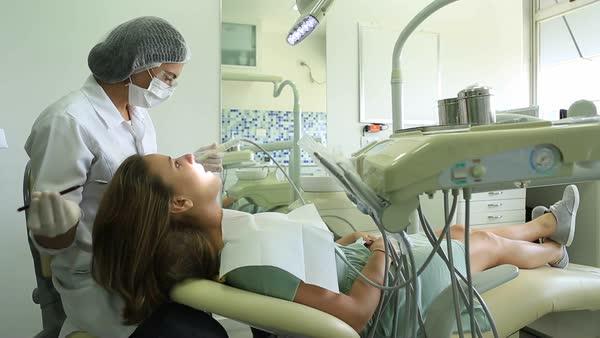 Female Dentist Examining Teeth Woman Working On PatientaEURTM