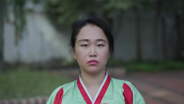 Slow motion shot of a woman in traditional Korean dress looking at camera Royalty-free stock video