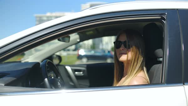 Beautiful woman wearing sunglasses and sitting in a car looks in the camera through open front window and smiles  Royalty-free stock video