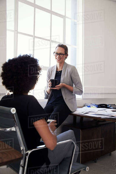 Two businesswomen having a coffee break in office, vertical Royalty-free stock photo