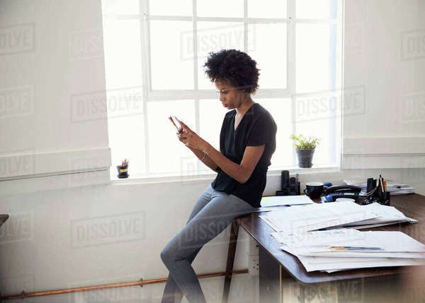 Young businesswoman sits on desk using phone in an office Royalty-free stock photo