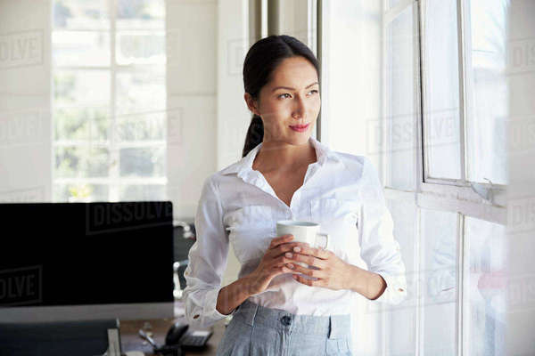 Young Asian businesswoman holding cup looking out of window Royalty-free stock photo