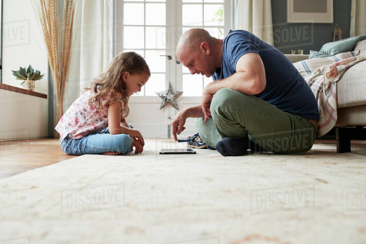 Girl and dad sit on the floor playing