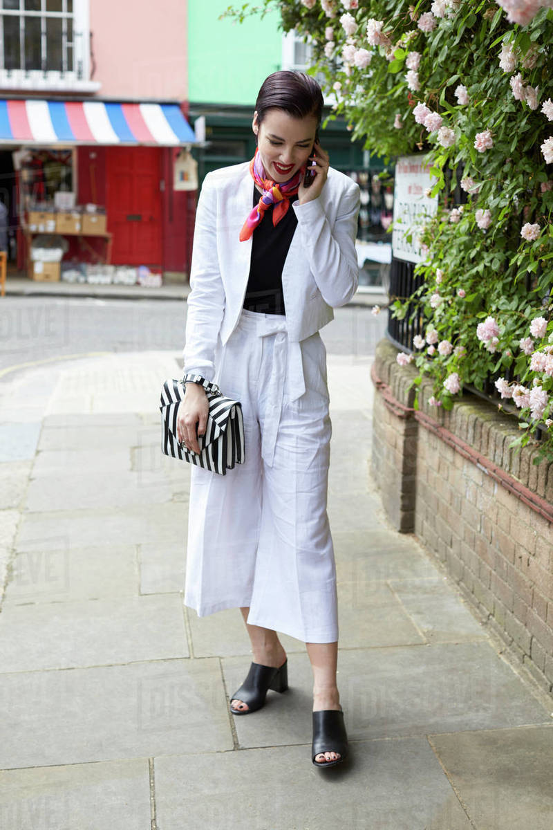 meet many fashionable uk cheap sale Woman in white linen suit using phone in street, full length stock photo