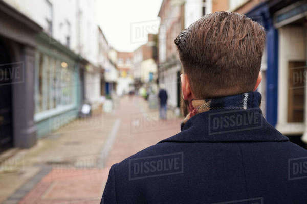 Rear view of young man walking down urban street Royalty-free stock photo