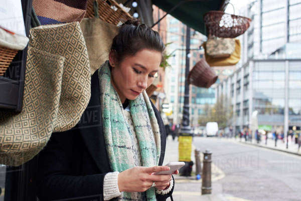 Young woman reading text message at outdoor market stall Royalty-free stock photo